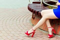 红色鞋子的美丽的长的腿女孩在蓝色礼服在城市坐 免版税库存照片