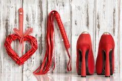 红色鞋子鞭子心脏在木背景扣上手铐 免版税库存图片