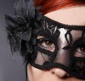 红色顶头妇女佩带的面具 库存图片