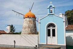 红色风车和教会在亚速尔群岛 免版税库存照片