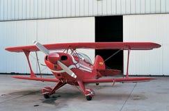 红色飞机和开放飞机棚门 免版税图库摄影