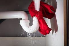 红色餐巾被栓在漏出水槽管子下 库存照片