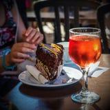 红色饮料由太阳,巧克力蛋糕,妇女手点燃了 免版税库存图片