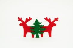 红色驯鹿和绿色圣诞树 免版税库存照片