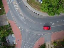 红色驾车横跨弯曲的交叉点在城市,鸟瞰图 免版税库存照片
