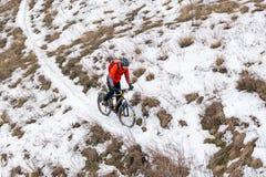 红色骑马登山车的骑自行车者在斯诺伊足迹 极端冬季体育和Enduro骑自行车的概念 免版税图库摄影