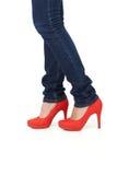 红色高跟鞋鞋子和牛仔裤 免版税库存照片