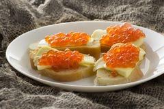 红色鱼子酱用黄油和被烘烤的面包 特写镜头 侧视图 图库摄影