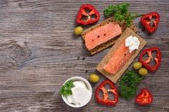 红色鱼用香料和黑麦面包在一张木桌上 与红色鱼和乳酪的三明治 库存图片