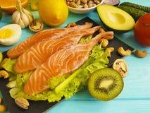 红色鱼,鲕梨,在蓝色木背景的有机坚果,新鲜健康的食物 免版税库存照片