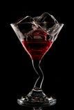 红色鸡尾酒。酒,马蒂尼鸡尾酒或者世界性在一块玻璃在黑背景。 库存照片
