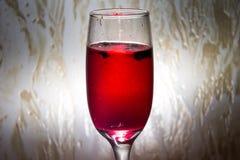 红色鸡尾酒用在一块透明玻璃的莓果 免版税库存图片