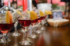 红色鸡尾酒用柠檬和在一张桌上的橙色身分在酒吧 免版税库存照片
