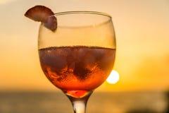红色鸡尾酒-在日落库拉索岛景色的饮料 免版税库存照片