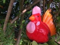 红色鸡玩偶在庭院里 免版税库存图片