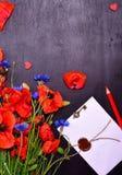 红色鸦片和蓝色矢车菊与一个被密封的信封 免版税库存照片