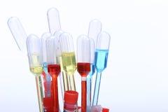红色,在吸管,许多的玻璃的蓝色黄色液体管 免版税库存图片