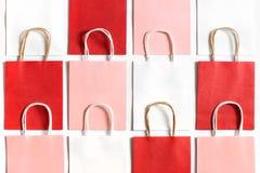 红色,桃红色和白色购物袋从回收在白色背景隔绝的纸 库存图片