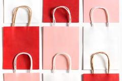 红色,桃红色和白色购物袋从回收在白色背景隔绝的纸 免版税库存照片