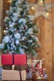 红色,棕色和含沙黄色圣诞节礼物和用杉木锥体和ashberry棍子装饰的蜡烛台在w的圣诞树附近 免版税库存照片