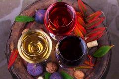 红色,玫瑰色和白色杯酒 葡萄、无花果、坚果和叶子在老木桶 看法从上面,顶面演播室射击 图库摄影