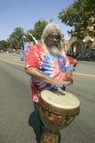红色,白色和蓝色领带染料T恤杉的嬉皮捣他的鼓下来大街在一次美国独立纪念日游行期间在Ojai,加州 免版税库存照片