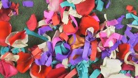 红色,白色玫瑰花瓣在一张绿色地毯驱散了 股票录像