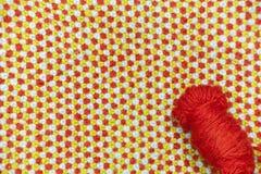红色,羊毛毛线缠结在被编织的,羊毛布料背景的  图库摄影