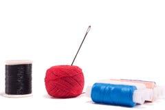 红色,蓝色,黑和樱桃颜色子线与针的 免版税库存照片