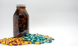 红色,黄色,绿色,蓝色抗药性胶囊药片和琥珀色的瓶,药物抗性 图库摄影