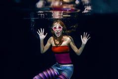 红色水下黑暗的背景的头发滑稽的女孩 免版税库存图片