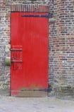 红色绘了与重的安全螺栓和砖墙的门 库存照片