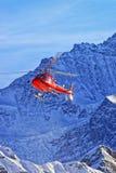红色直升机在瑞士阿尔卑斯在冬天阳光下 库存图片