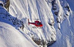 红色直升机在瑞士阿尔卑斯少女峰地区 免版税库存照片