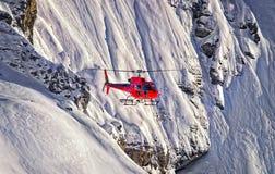 红色直升机在瑞士阿尔卑斯少女峰地区 库存照片