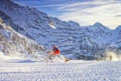 红色直升机离开在瑞士滑雪胜地靠近少女峰登上 免版税库存照片