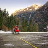红色直升机登陆了在瑞士直升机场在少女峰地区 免版税库存图片