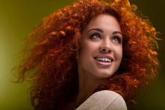 红色头发。有卷曲长的头发的美丽的妇女。优质ima 库存图片