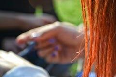 红色头发和一未聚焦的woman& x27; s手 库存照片