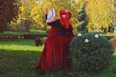 红色头发妇女浪漫画象红色明亮的礼服的有爱好者的由纸牌做成 心脏的女王 创造性的概念 库存图片