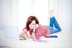 红色头发学生,说谎的女商人下来研究膝上型计算机 免版税库存图片