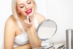 红色嘴唇。做每日构成的美丽的妇女。唇膏申请 免版税库存照片
