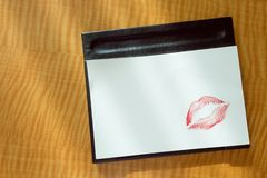 红色嘴唇亲吻白色空白的在桌上的笔记性感的早晨消息 免版税库存照片