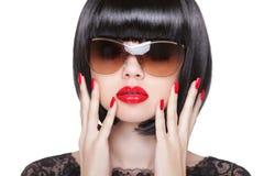 红色嘴唇构成和被修剪的波兰钉子 美丽的黑色深色的方式头发健康构成 免版税库存照片