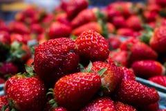 红色水多的草莓在市场上 免版税库存图片