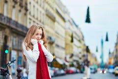 红色围巾的美丽的女孩在一条巴黎人街道上 免版税图库摄影