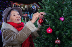 红色围巾的老妇人装饰圣诞树的 库存图片