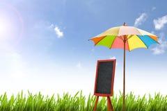 红色黑板被安置在有绿色领域的一把五颜六色的伞下 库存照片