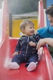 红色幻灯片的愉快的婴孩微笑对母亲的 图库摄影