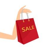 红色购物袋在妇女的手上 免版税库存图片